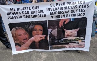 "A sign featuring a popular meme reads: ""You told me that the San Rafael mining company would bring development! Yes, but only for the investors and the companies that sell you all services."""