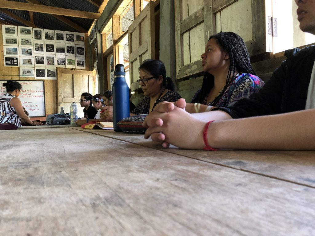 Students listen to community leaders tell the story of Copal AA's founding. Photo credit: Chantelle John