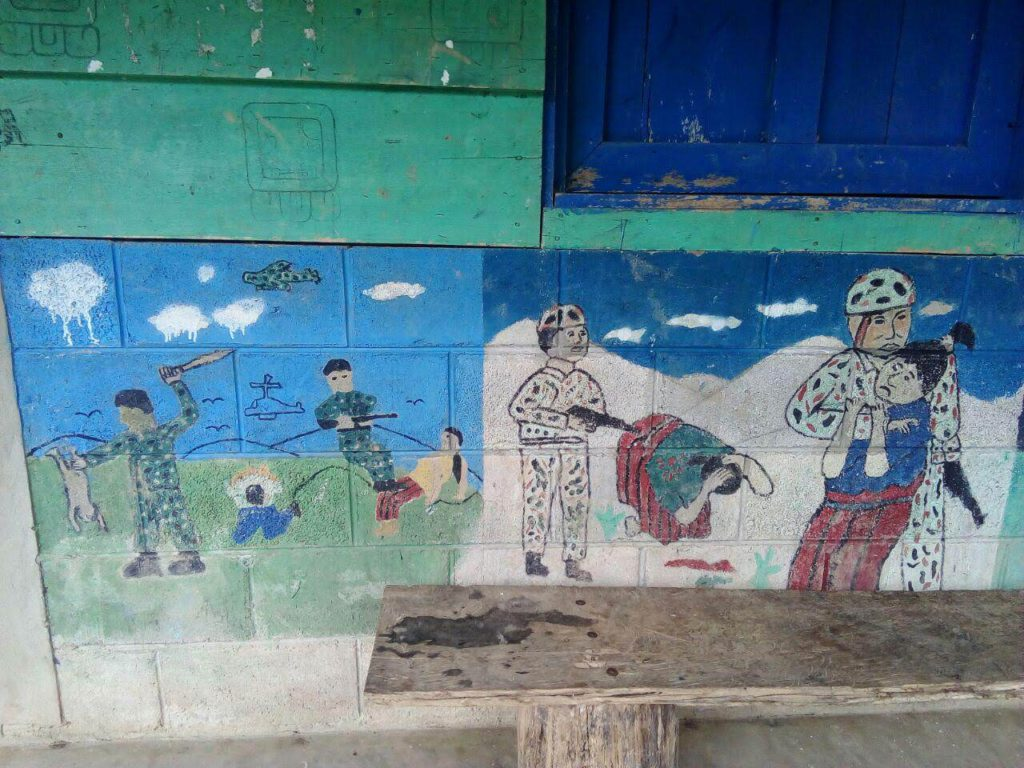 A community in Copal AA La Esperanza, Cobán, Alta Verapaz, depicts the horrors that community members lived during the internal armed conflict. Murals and other public art serve to maintain historical memory of the massacres and heal the survivors. The murals depict soldiers abusing children and women. There are blood stains painted into the ground and helicopters in the sky. Above the mural, on the green painted wood, are images of Mayan nahuales.