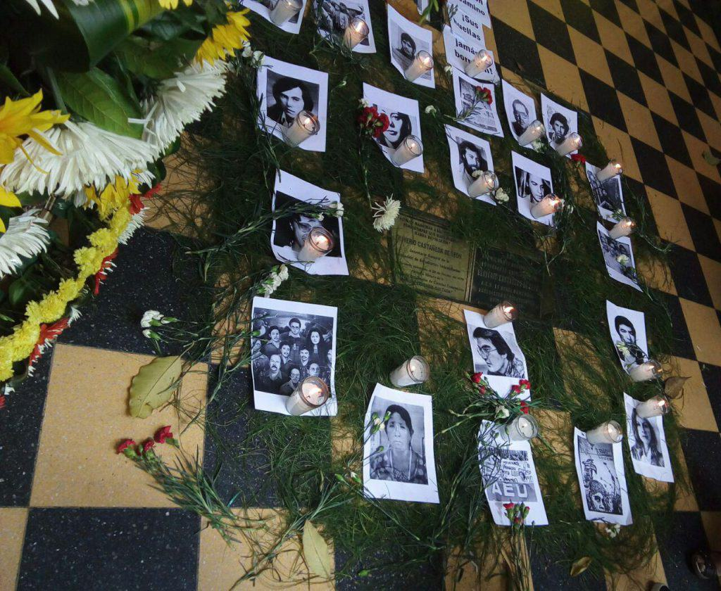 Pictures of disappeared people are placed with candles around a plaque marking the site where student organizer Oliverio Castañeda de León was assassinated.