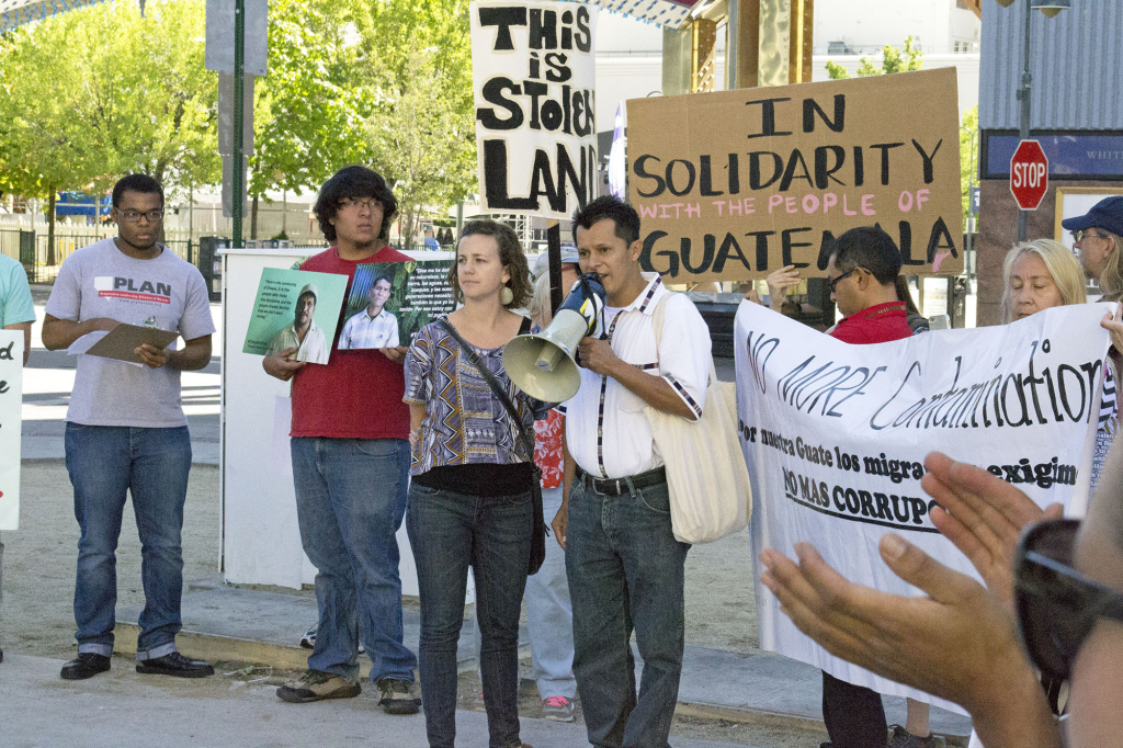 "NISGUA tour speaker Llan Carlos speaks into a megaphone at a protest in Reno, Nevada. Behind him are people holding signs, ""This is stolen land,"" and ""In solidarity with the people of Guatemala."""