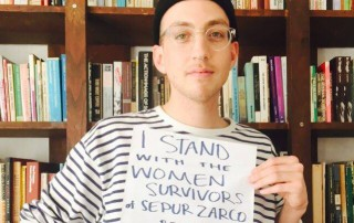 "A person stand in front of a bookshelf with a sign that read ""I stand with the women survivors of Sepur Zarco."""