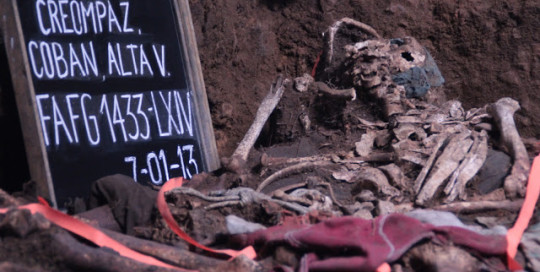 "Left side shows a chalkboard reading ""CREOMPAZ, Alta Verapaz"" and the date, July 1, 2013. Next to the chalkboard are the uncovered human remains in an exhumed pit."
