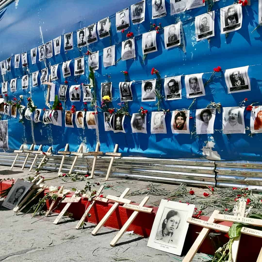Picture of a giant poster with Guatemalan national colours, covered by pictures of the dissapeared and murder during the Internal Armed Conflict along with red carnationsand crosses with their names.
