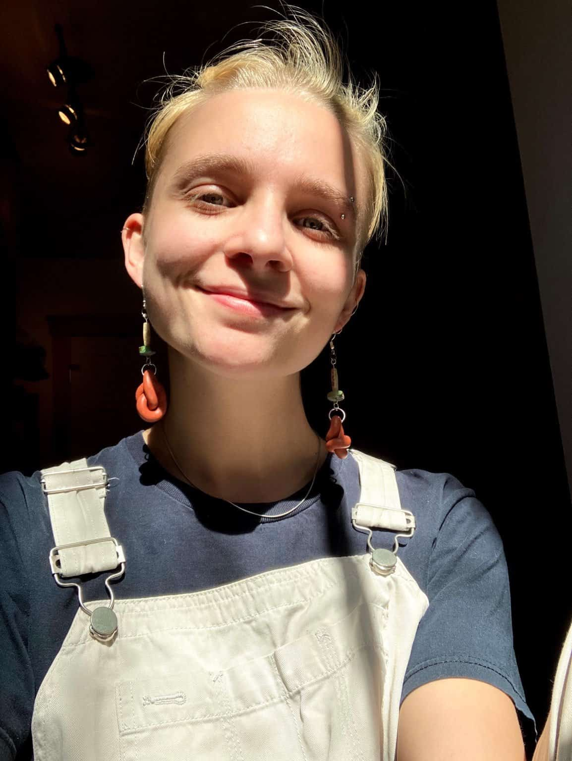 Oli a white non binary presenting person, smiling for the camera, wearing a beige overall, blue navy shirt and orange earnings.