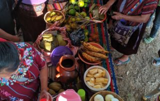 Women gather around a brightly colored table laden with fruits and drinks.
