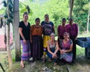 Seven women smile together, three in traditional Maya Q'eqchi' clothing. Bright green forest is behind them.