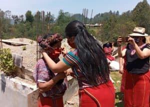 Una representante de la AJR le ayuda a pobladora a ponerse mascarilla. Foto: AJR