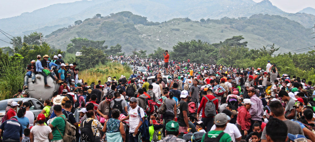 Asylum seekers fill the road while walking through Oaxaca, Mexico. In the background are rolling green hills. People are mostly on foot, and their clothing is bright and colorful in the foreground.