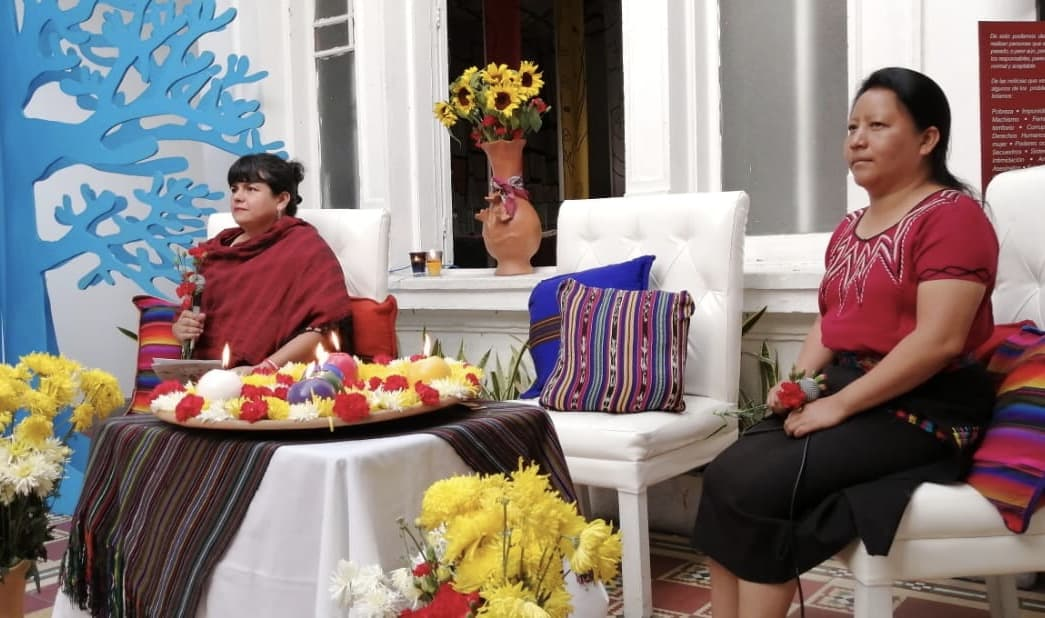 On the left corner there are yellow flowers and a cartoon blue tree. A woman dressed in red holds a microphone. In the center, there is a flower and candles offering. On the right another woman dressed in red and black, also holds a microphone and a red flower.
