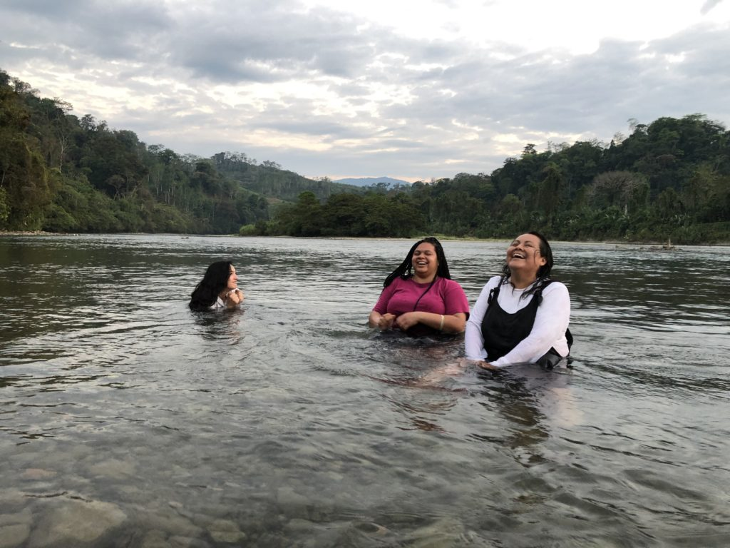 Delegates Adrienne, Toteona, and Kori laugh in the Chixoy river. Photo credit: Chantelle John