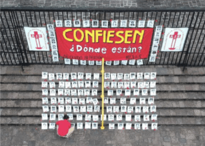"""Alt text: Outside a fence there is a sign that reads """"Confess: Where are they?"""" On the stairs, a person with a red t-shirt is laying the black and white pictures of the 183 disappeared who are registered in the Military Diary."""