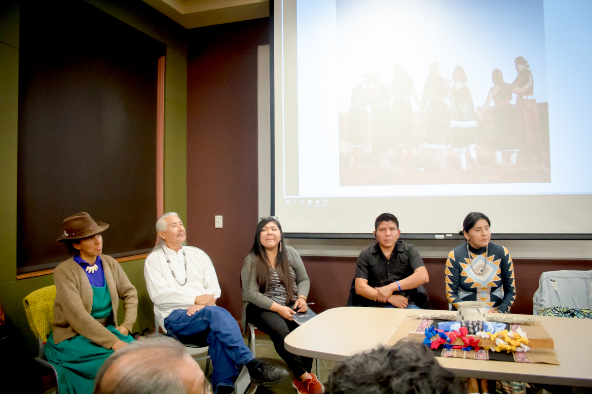 A photograph of Indigenous people sitting in a speaking panel.