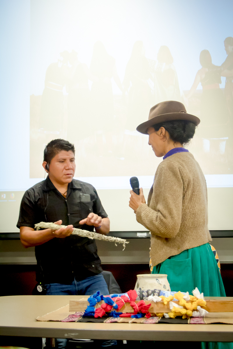 A photograph of a person in a skirt and hat handing sage to a man in a black shirt.