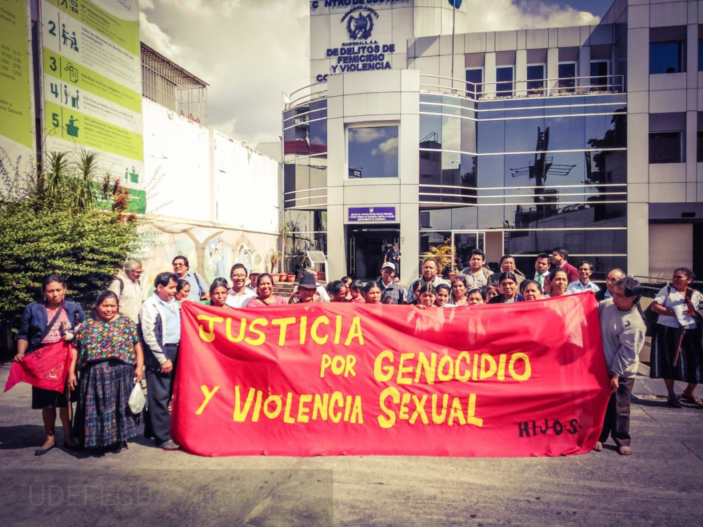 Communities Affected by Military Zone 21 Violence Call for Justice for Genocide and Sexual Violence. People hold a huge red banner that reads: