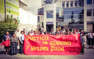 "Communities Affected by Military Zone 21 Violence Call for Justice for Genocide and Sexual Violence. People hold a huge red banner that reads: ""Justice for genocide and sexual violence / H.I.J.O.S."""