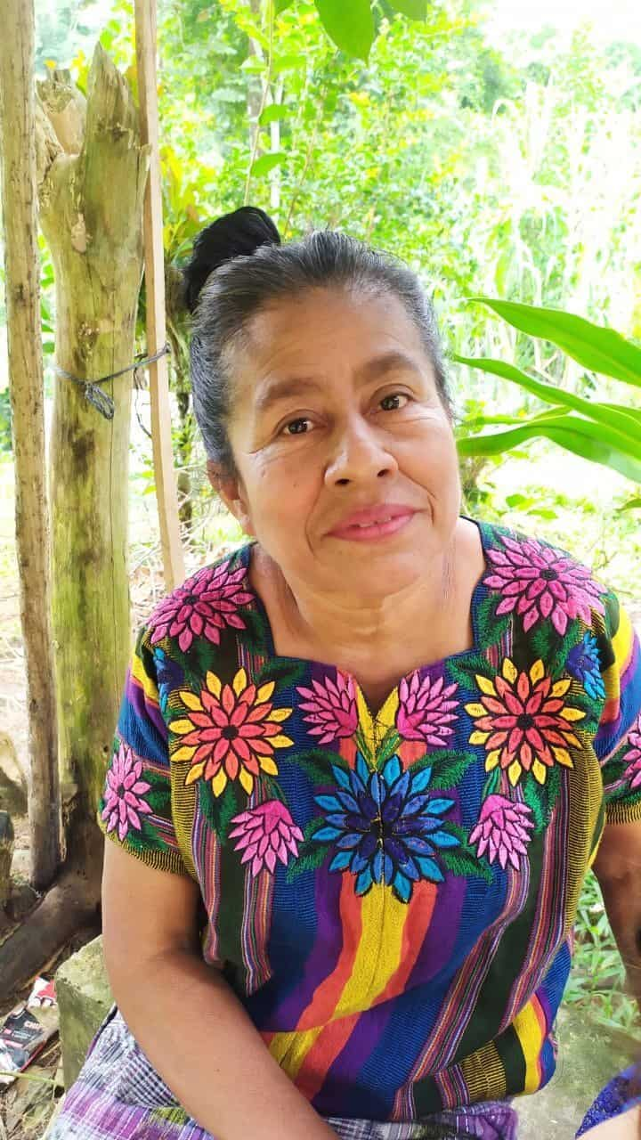 A photograph of Dolores Cu wearing a colorful huipil in front of a bright green background