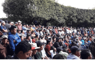 The picture shows a meeting of hundreds of people on Barillas waiting and hearing to someone not shown. Behind them there are trees and people are protecting themselves from the sun