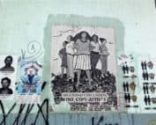"""Street art in a wall at Guatemala City depicting in the center an image of women standing and protecting themselves with the legend """"Security with justice not with weapons"""". In the left, pictures of disappeared during the Internal Armed conflict and of Jackelin Call who died under ICE custody. To the right a graffiti showing different couples equals love"""