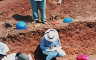 FAMDEGUA is supervising and exhumation on Los Josefinos Village, there are three people on the ground searching for bones and one person standing in front of a sign that says FAMDEGUA