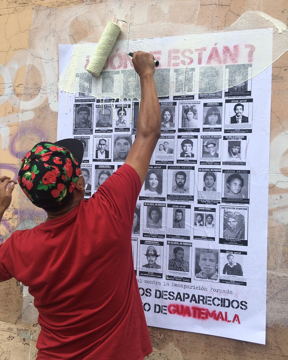 A man with a red t-shirt and a hat is posting a sign with faces of the disappeared. On top on red the sign reads Where are they?