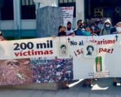 On the left a woman holds both a picture of a disappeared love one and a sign that reads 200, 000 victims. On the other side, there are a group of 10 people behind a sign that reads No to militarism, yes to Peace! All of them are wearing masks.