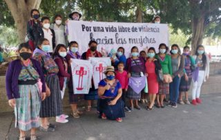 A group of women wearing facemask and some of them purple scarfs pose in Guatemala Central Park during the International Women´s day conmemoration, some of them hold a sign that reads: For a life free of violence against women""