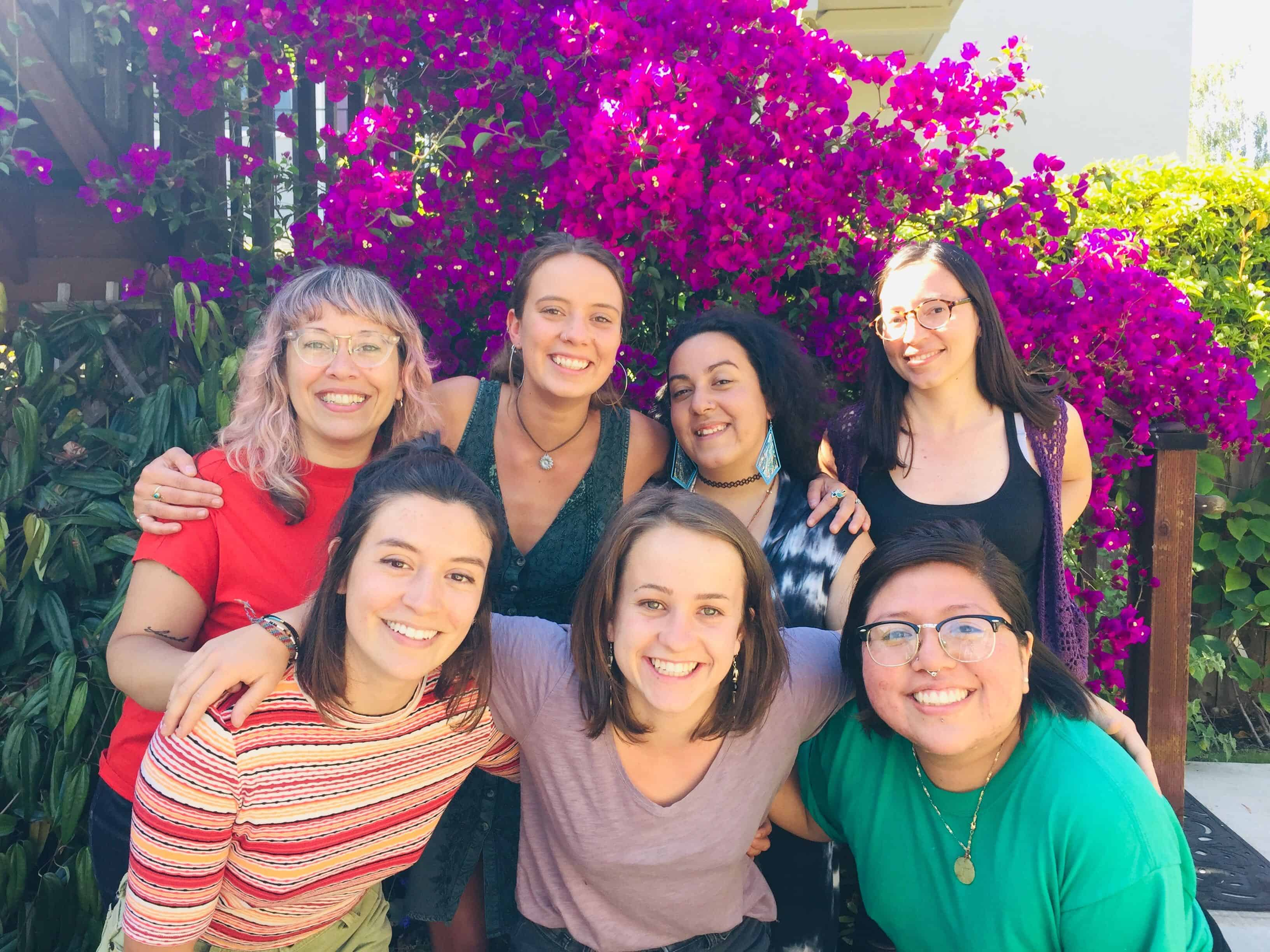 A photograph of 7 smiling people of color in front of a blooming tree.