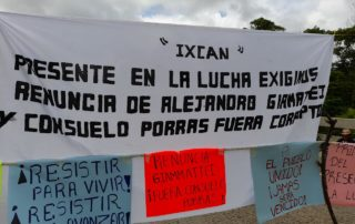In the middle of a road, you can see clouds in the background, there is a white blanket that says Ixcán present in the fight, we demand the resignation of Alejandro Giammattei and Consuelo Porras. Below on the left a blue sign that says Resist to Live, Resist to Advance. Next, an orange sign that says resign Giammattei! And Porras Out! on the right side a sign says the people united will never be defeated.