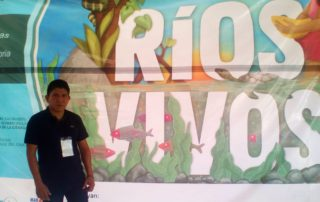 José Gómez stands in front of a sign that read RIOS VIVOS, or LIVING RIVERS.