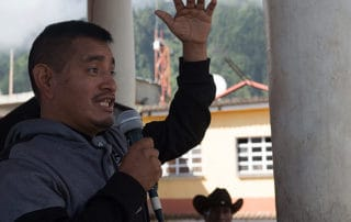 A photograph of a man speaking into a microphone with his hand raised for emphasis.