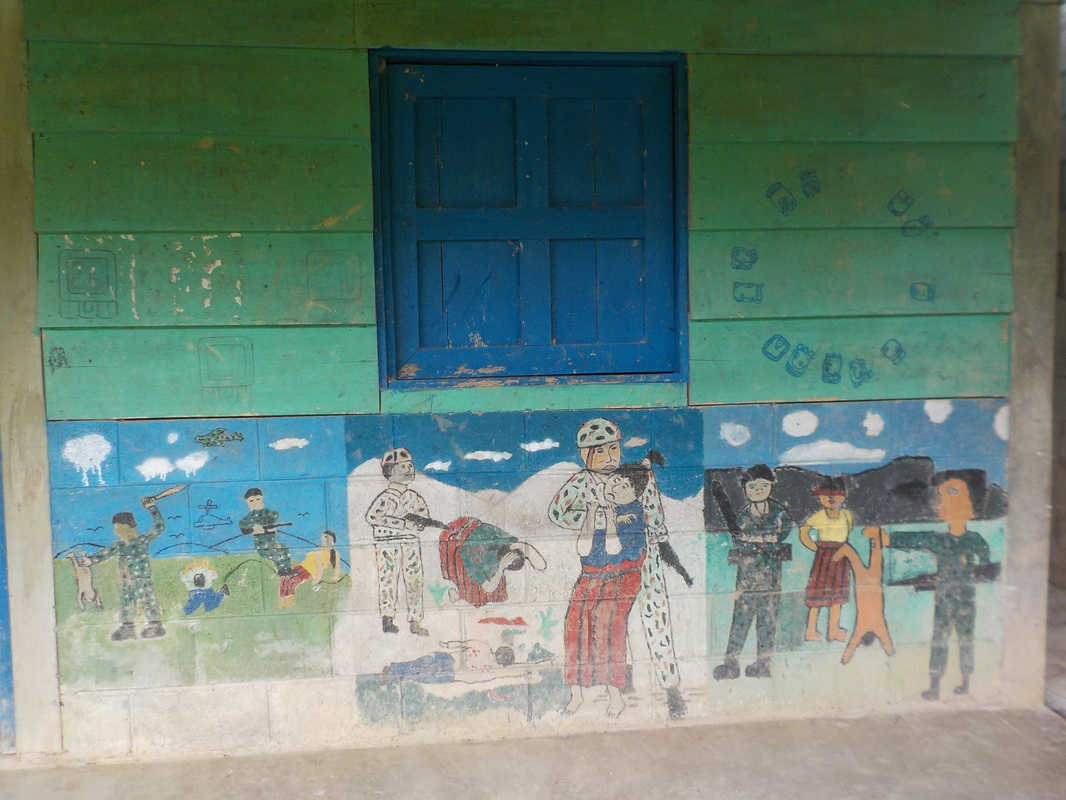 A painting of a school room. The upper wall has green paint with blue windows and in the below there is a mural painted by children depicting scenes of the attacks on Indigenous Communities during the Internal Armed Conflict