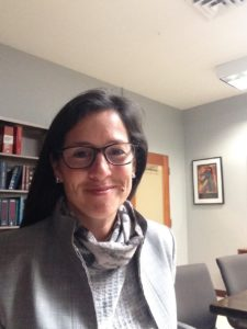 Photograph of Lydia Lopez smiling in an office. She is femme with long dark hair and is wearing a grey suit.
