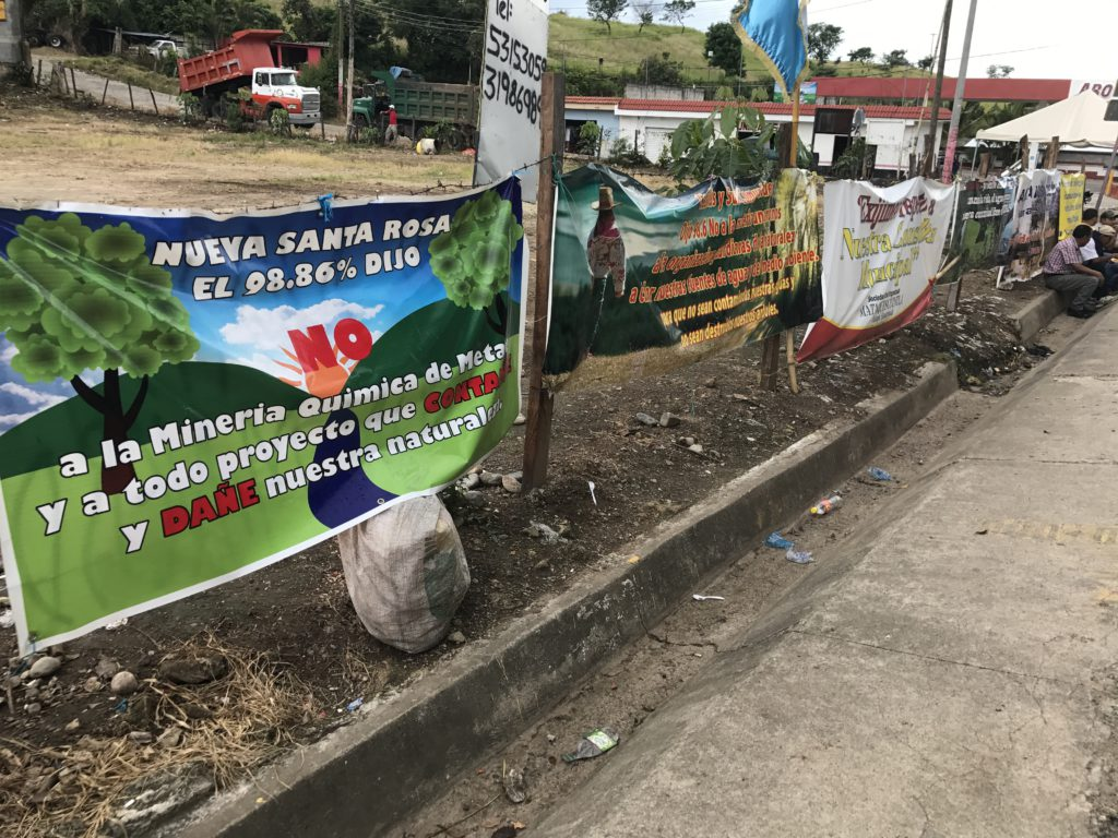 "People gather at the resistance camp in Casillas. The nearest sign reads: ""98.86% of Santa Nueva Rosa said NO to the chemical metal mine and all projects that contaminate and hurt our environment."""