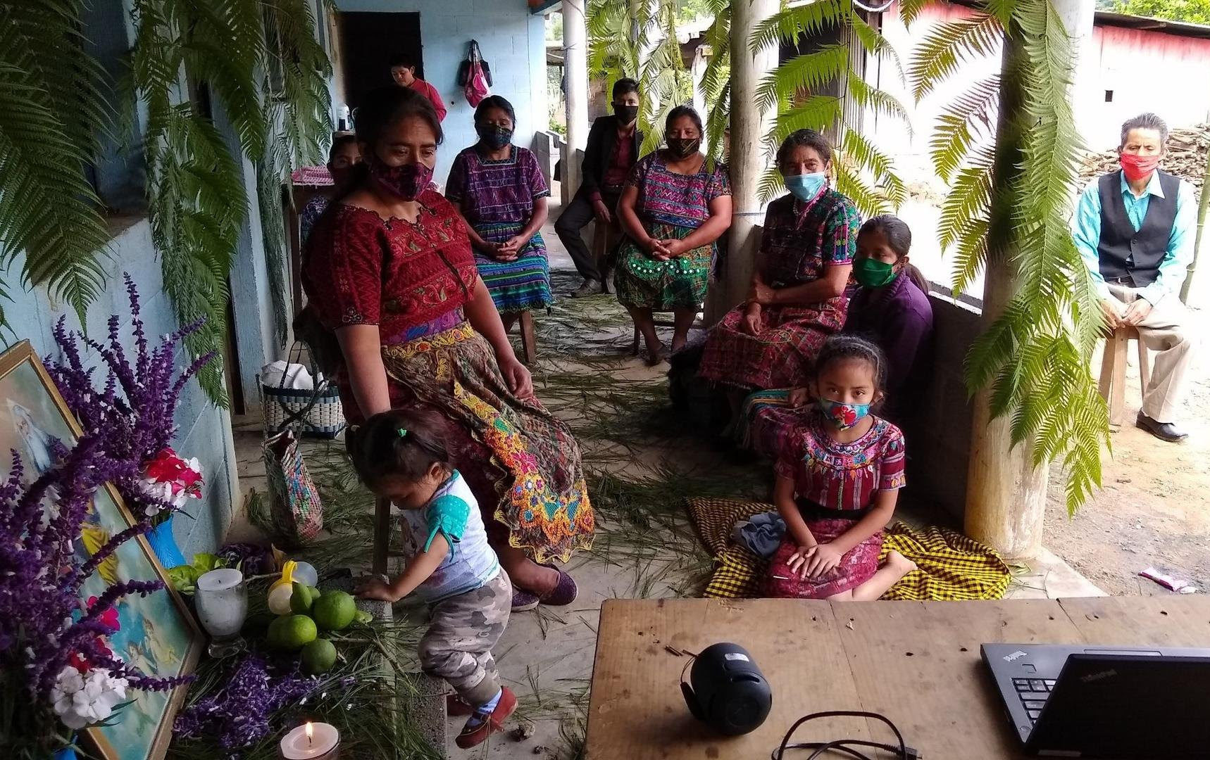 In the front of a house, 9 people, mostly women, all using facial masks are sitting in the distance while they watch the livestream of the assembly on a laptop. There is a small altar on the left side, where a child plays.