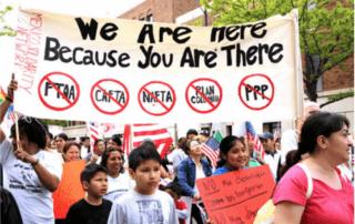 """imagen de un grupo de personas manifestando. La multitud se compone principalmente de mujeres y niñxs. Se sostiene una pancarta con las palabras """"Estamos aquí porque tú estás allí""""."""