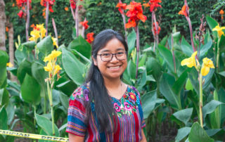 Photograph of a smiling young person in a Mayan huipil in front of bright green, red, and yellow flowers.