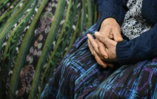 A woman folds her hands over her Mayan skirt, or corte.
