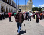 A photograph of Rubén Herrera from behind. He is a tall man walking with dignity and a cane towards a crowd of people. On the right are people holding signs wearing traditional Mayan clothing, on the left a line of police in uniform.