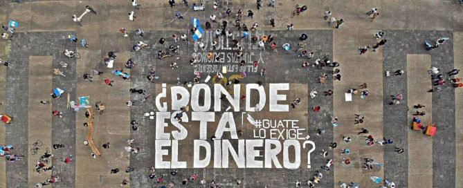 """Aerial photo of Plaza de la Constitución in Guatemala City. There are people protesting while social distancing and a couple of Guatemalan flags can be seen. In the center of the picture it is written in white paint """"Dónde está el dinero? Guate lo exige"""", Where is the Money? Guate Demands it"""". The remains of other protests can also be seen, as under as below the main white letters, you can read in black Si hubo genocidio, yes, there was a genocide and the number 56 in yellow, reffering to the murders of the girls in the Hogar Seguro Case."""