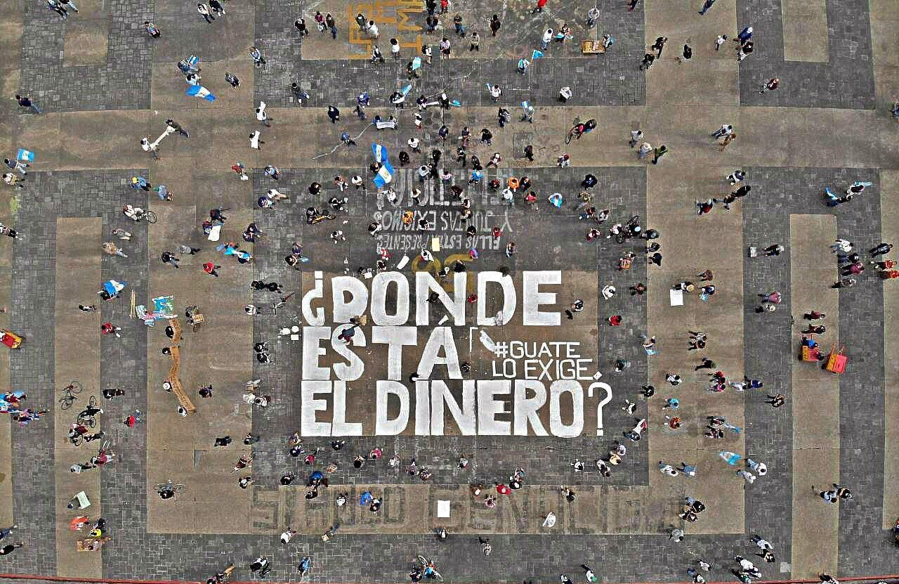 "Aerial photo of Plaza de la Constitución in Guatemala City. There are people protesting while social distancing and a couple of Guatemalan flags can be seen. In the center of the picture it is written in white paint ""Dónde está el dinero? Guate lo exige"", Where is the Money? Guate Demands it"". The remains of other protests can also be seen, as under as below the main white letters, you can read in black Si hubo genocidio, yes, there was a genocide and the number 56 in yellow, reffering to the murders of the girls in the Hogar Seguro Case."