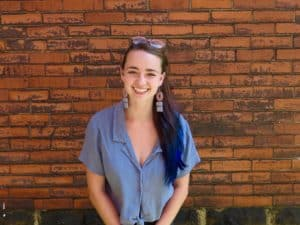 Photo of Zia Kandler smiling in front of a brick wall. She is a white femme with long brown hair with blue tips.