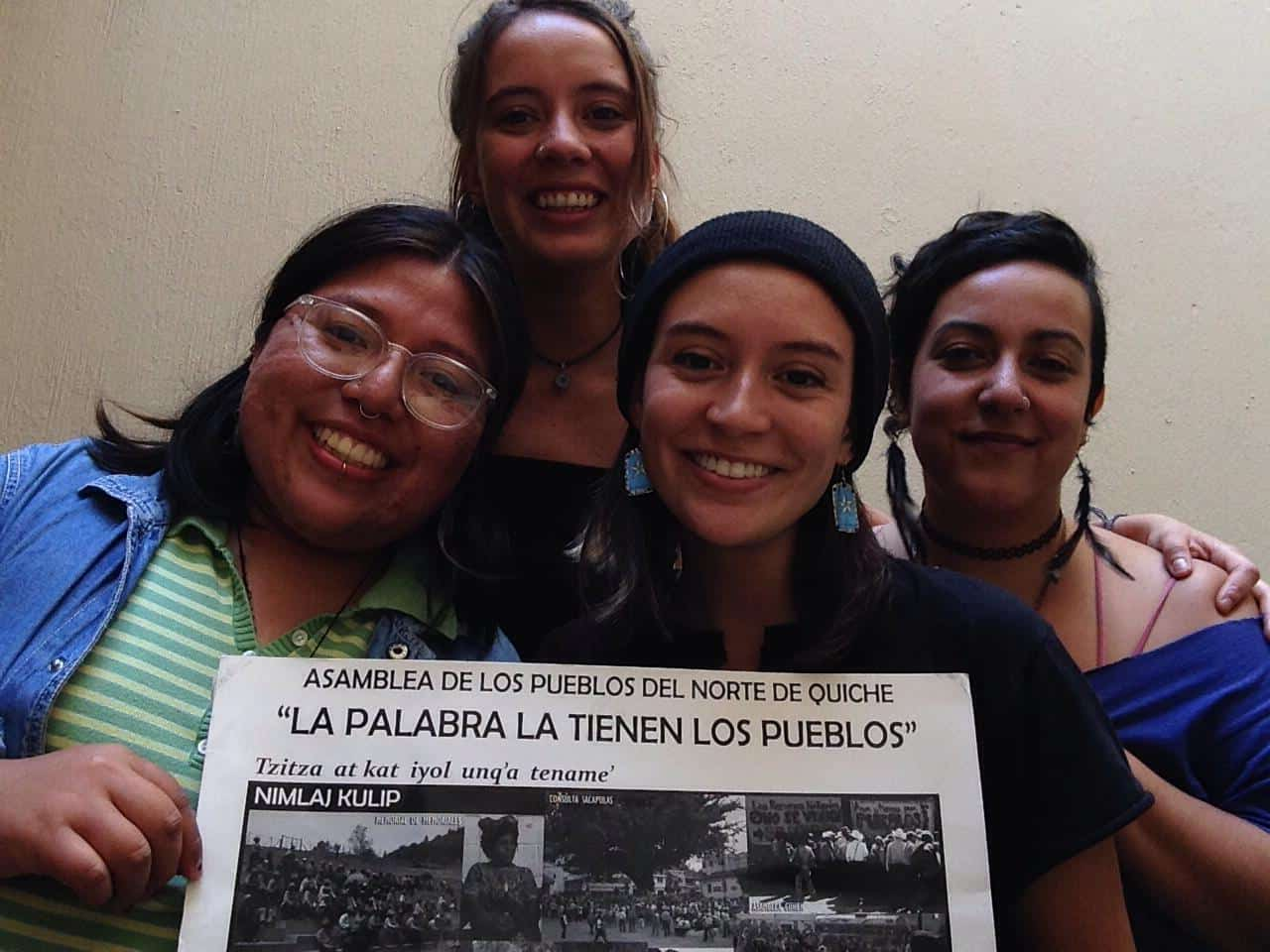 4 NISGUA accompaniers hold a sign that says