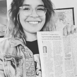 Photograph of a smiling femme with glasses holding a newspaper. The headline reads