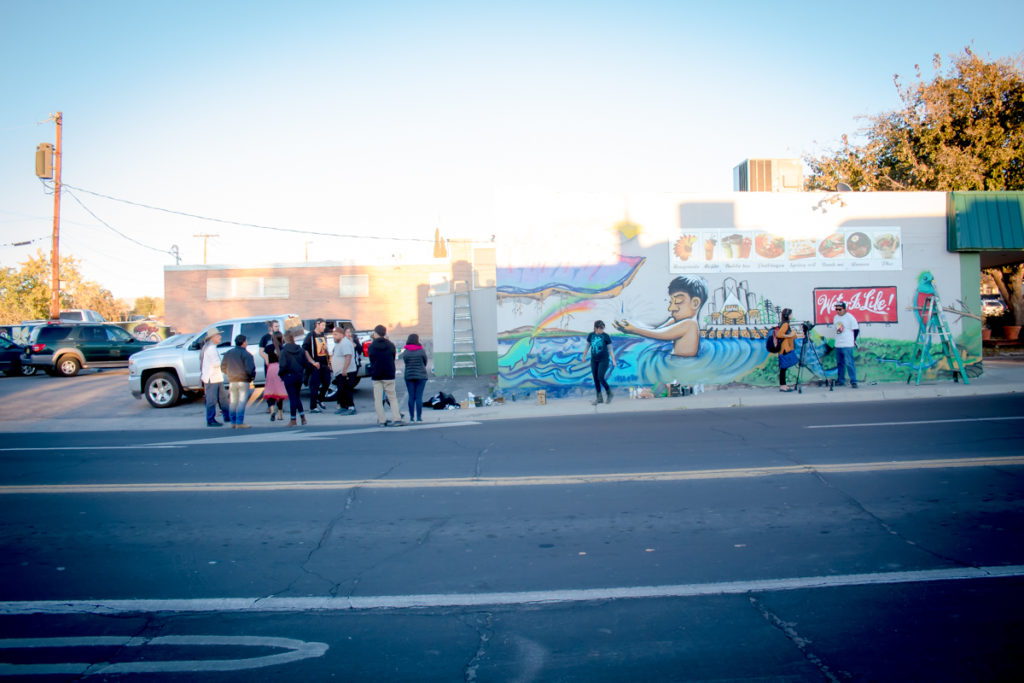 A photograph of people gathering around a mural.