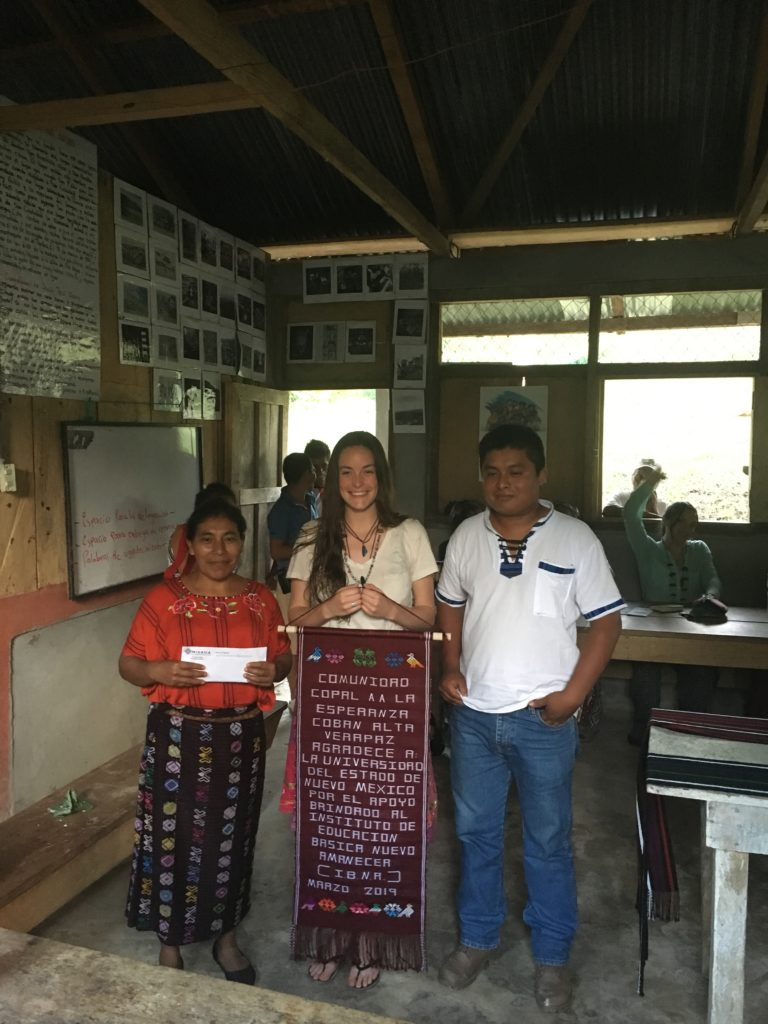 Kayla poses with members of the local Community Development Committee (COCODE), Fabiana and Enrique, holding Copal AA's gift to the delegation.