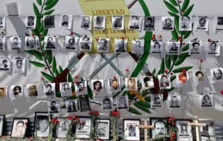 Covering a giant poster with guatemalan national symbols, organizations put in the front pictures of the dissapeared and murder during the Internal Armed Conflict along with red carnations and crosses