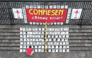 """Outside a fence there is a sign that reads """"Confess: Where are they?"""" On the stairs, a person with a red t-shirt is laying the black and white pictures of the 183 disappeared who are registered in the Military Diary"""