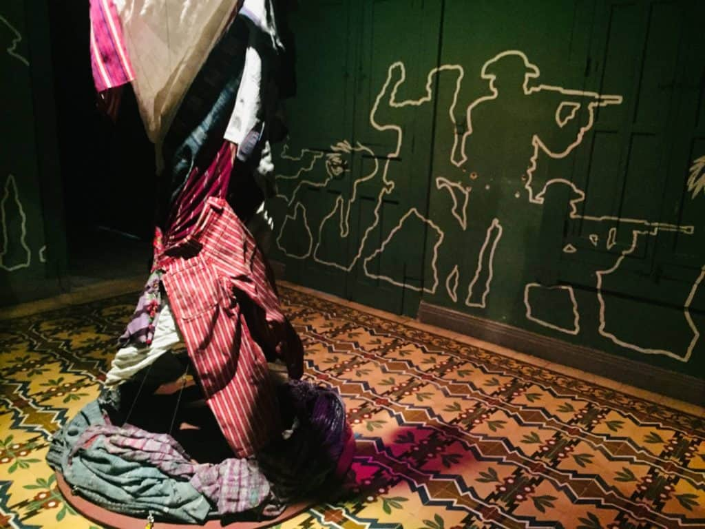 Pieces of clothing wrap around a stand in a tornado formation with outlines on the wall behind telling the story of soldiers hunting down civilians.