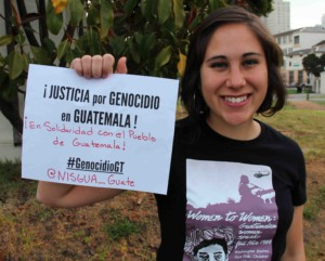 "A photograph of a NISGUA organizer holding a sign that reads ""Justicia por genocidio en Guatemala!"""